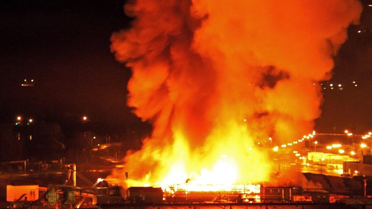 Des flammes et de la fumée provenant d'un édifice en feu s'élancent vers le ciel la nuit.