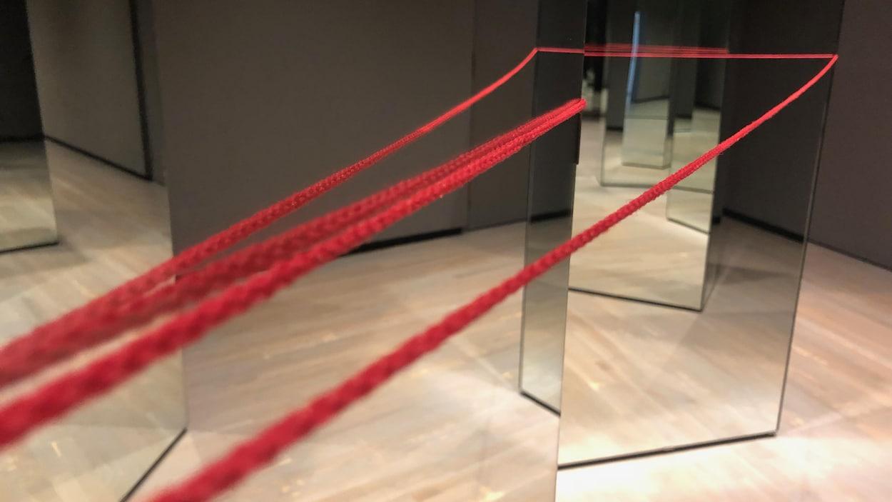 Quatre fils rouges sont tendus et se redent en direction de plusieurs miroirs.