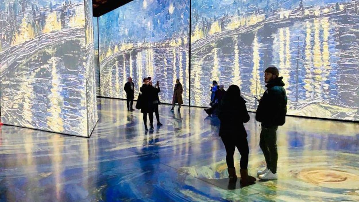 Des gens dans une grande pièce colorée observent d'immenses panneaux lumineux mettant en scène des tableaux du peintre Van Gogh.
