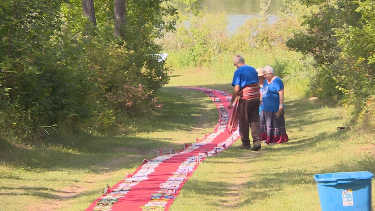 Deux femmes et un homme debout près d'un long tapis rouge installé sur le gazon.