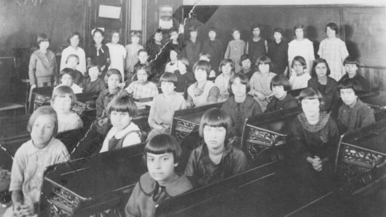 Des fillettes sont assises en rang et regardent l'objectif de la caméra.