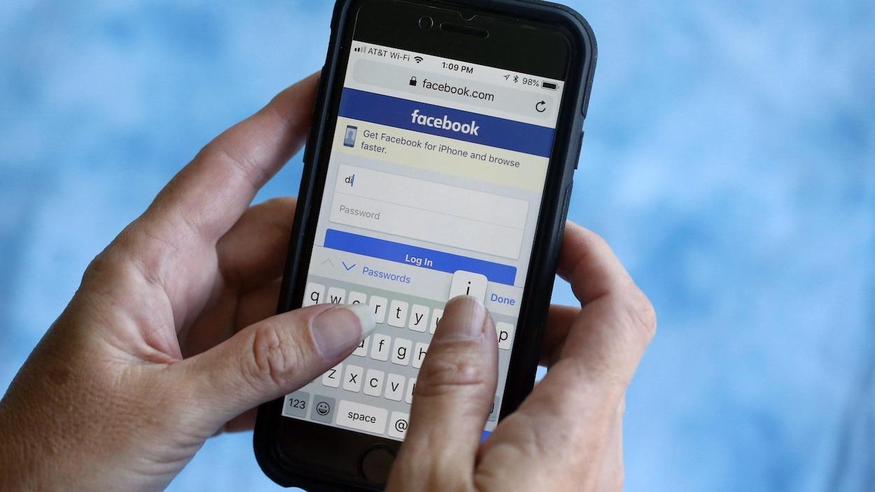 Une personne écrit un message via Facebook sur son cellulaire.