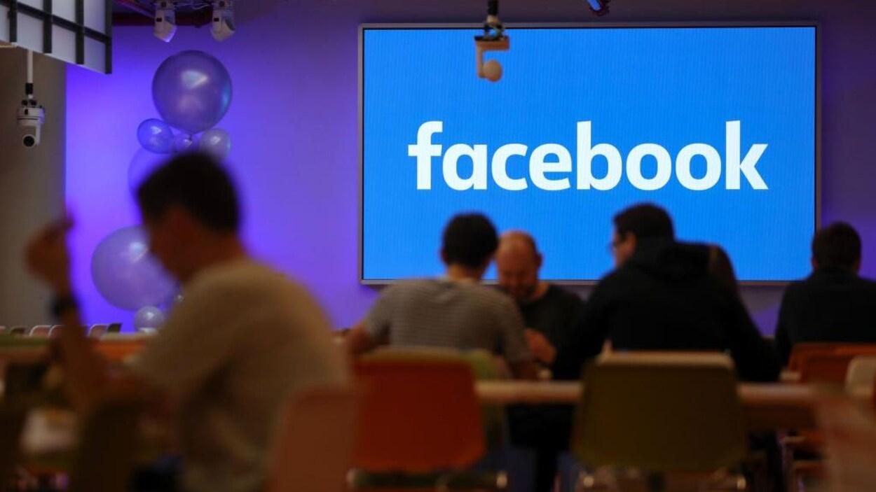 Des hommes déjeunent à table dans une grande salle, avec en fond un écran bleu affichant le logo de Facebook.