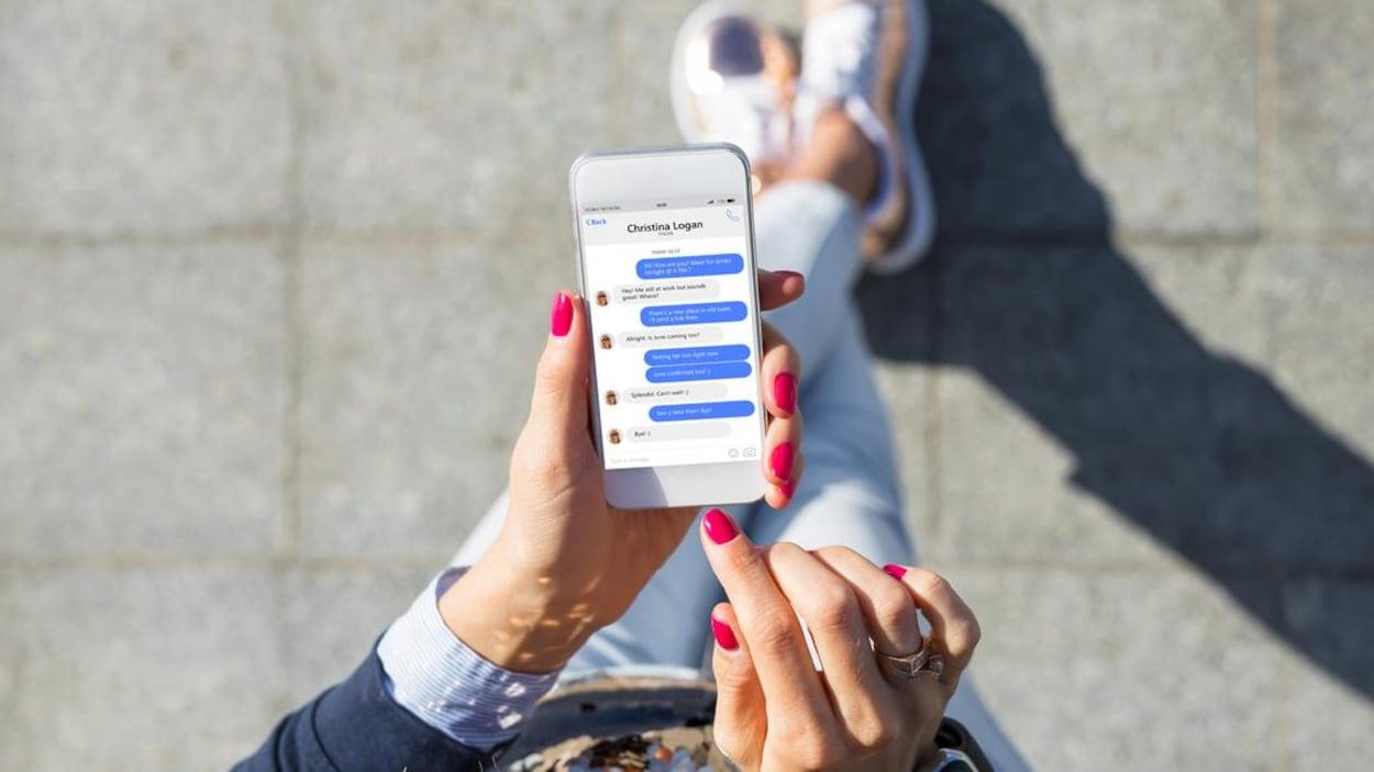Vue en plongée de l'écran d'un téléphone intelligent qui montre une application de messagerie utilisée par une femme.