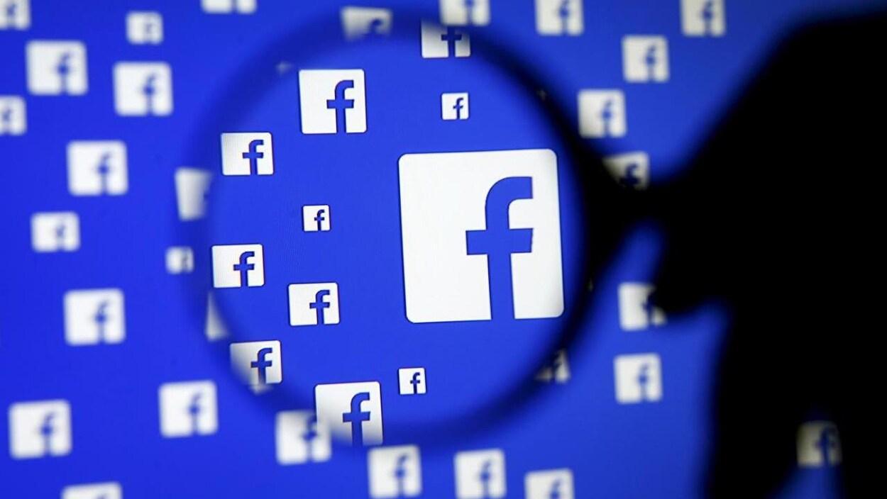 Plusieurs logos de Facebook sur un écran, vus par une loupe.
