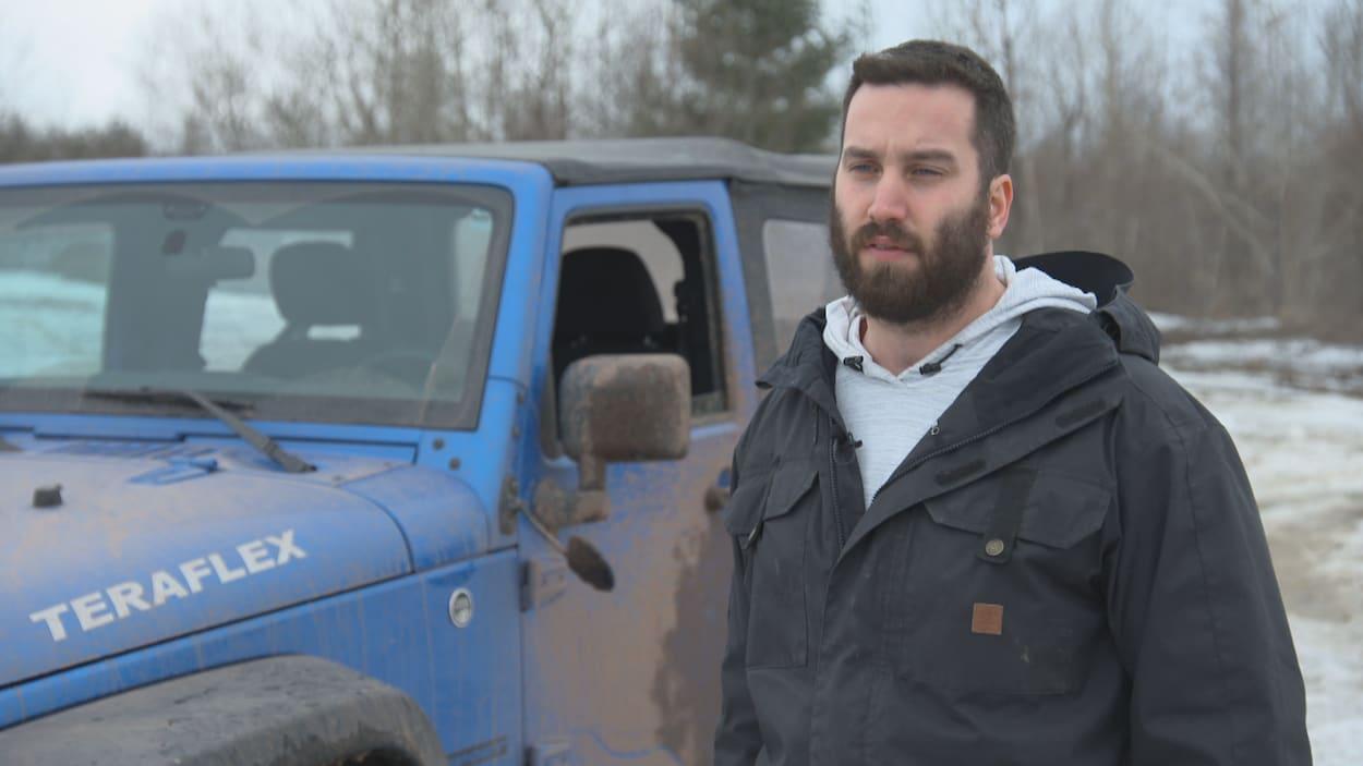 Shawn Leblanc, portant un manteau noir, discutant avec le journaliste lors d'une entrevue devant son véhicule Jeep bleu.