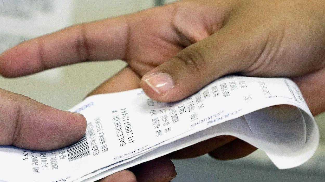 Deux mains s'échangent un ticket de caisse.