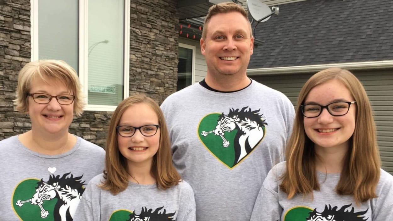 Rene Cannon, son mari ainsi que leurs deux filles, Abbie et Tessa, prennent une photo devant leur maison.  Ils sourient et portent des T-shirt à l'éfigie du cheval des Broncos dans un coeur.