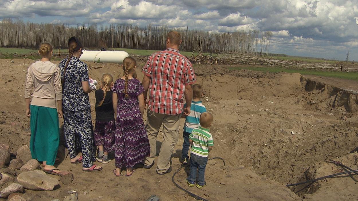 La famille Peters de dos fait face au trou laissé par la démolition de sa maison brûlée.