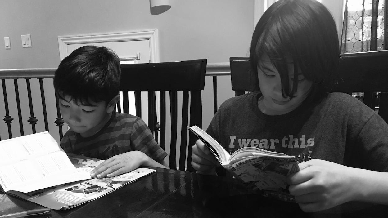 Les deux garçons sont en train de lire, assis à table.