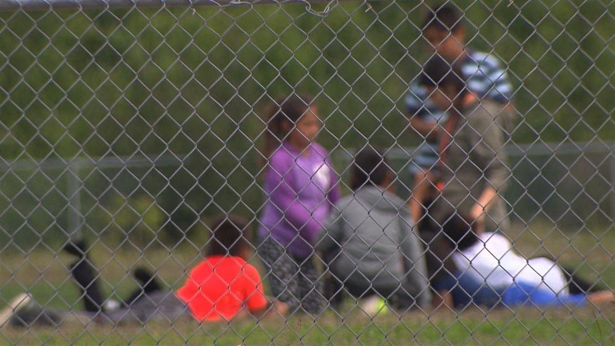 Des enfants autochtones dans une cour d'école.