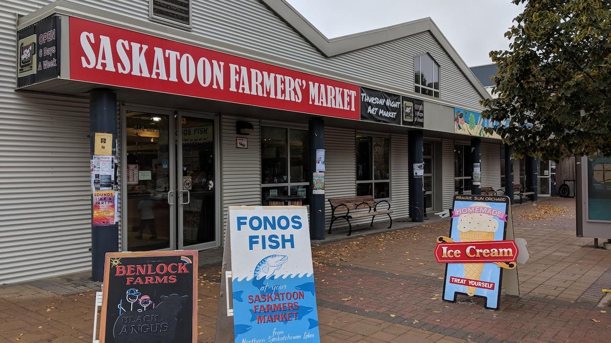 Devanture de l'édifice du marché des fermiers de Saskatoon avec des pancartes commerciales, sous un ciel gris.