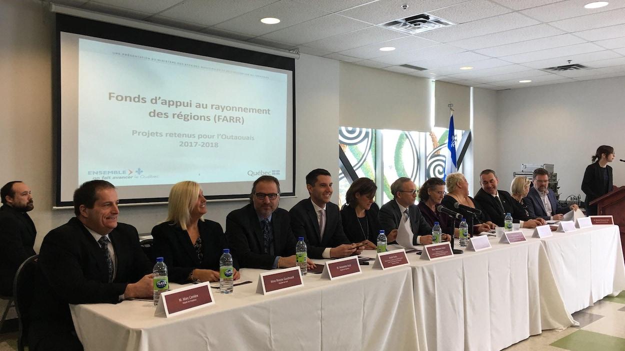 Les cinq députés provinciaux de l'Outaouais sont assis à une table avec le ministre Coiteux et des élus municipaux.