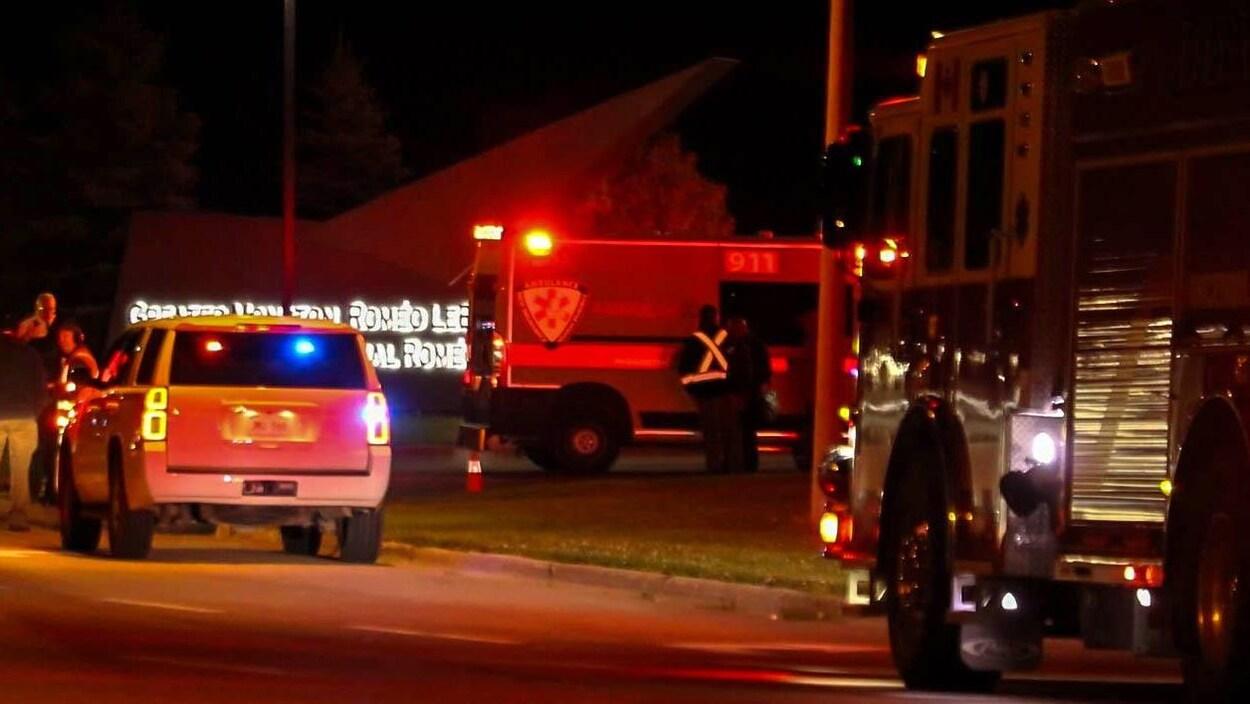 Véhicule de police, ambulance et camion de pompiers près de l'enseigne à l'entrée de l'aéroport.