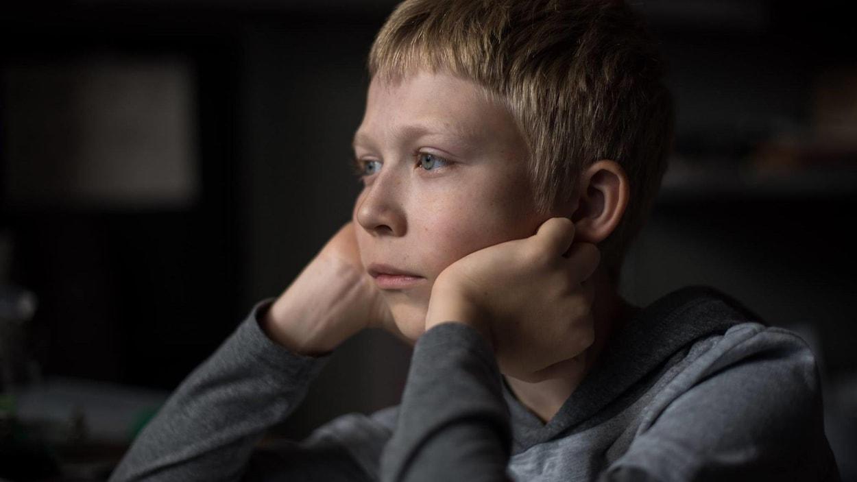 Un enfant blond, sa tête posées dans ses mains, les coudes sur son bureau, regarde au loin, dans une scène du film <i>Faute d'amour</i>.
