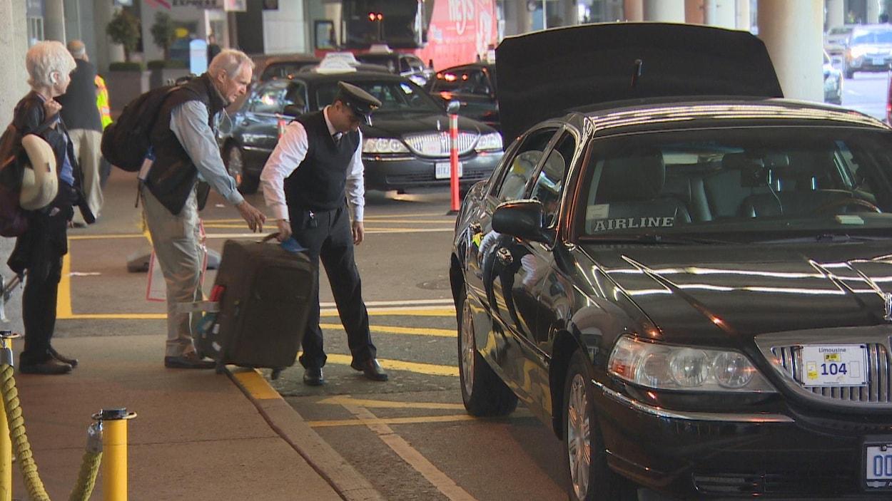Un couple de voyageurs s'apprête à embarquer dans un taxi.