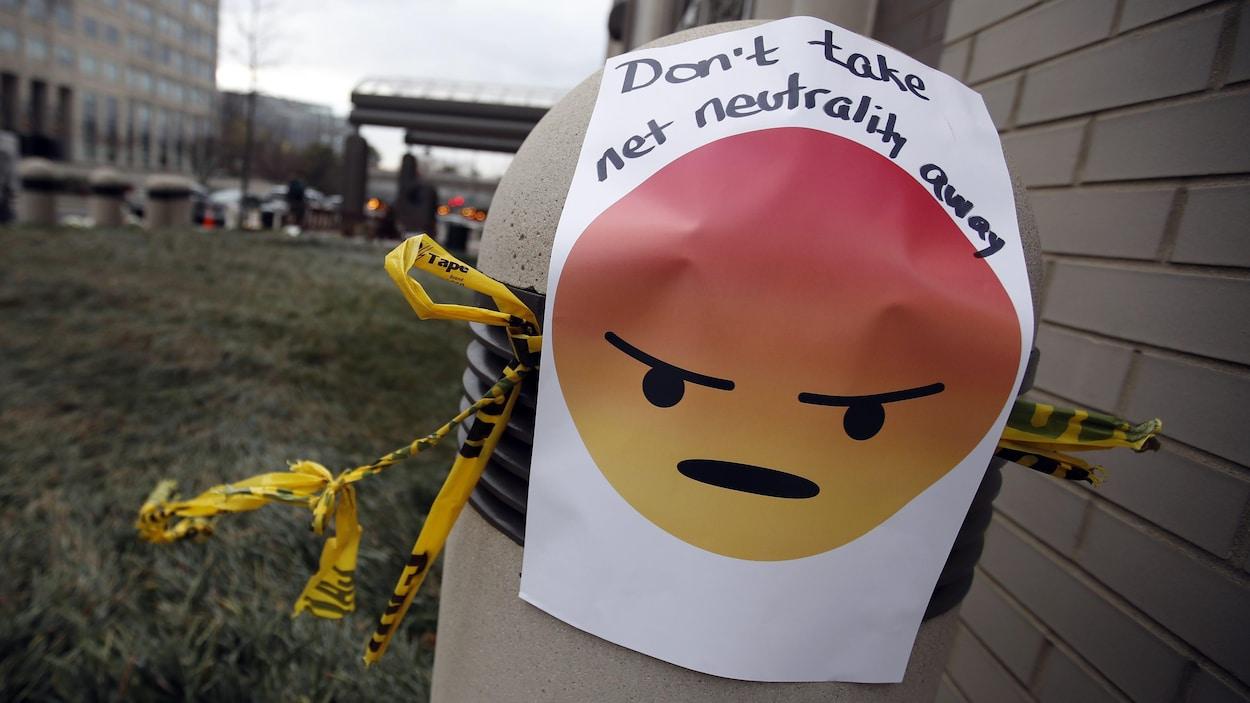 Une affiche avec un émoticône et le message « N'enlevez pas la neutralité d'Internet », placée à l'extérieur des bureaux de la Federal Communications Commission (FCC) à Washington le 14 décembre 2017.