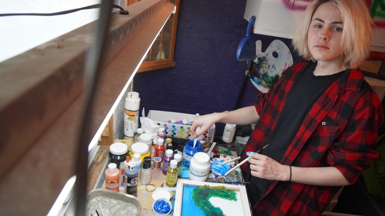 Félix dans son atelier avec des pinceaux en main.