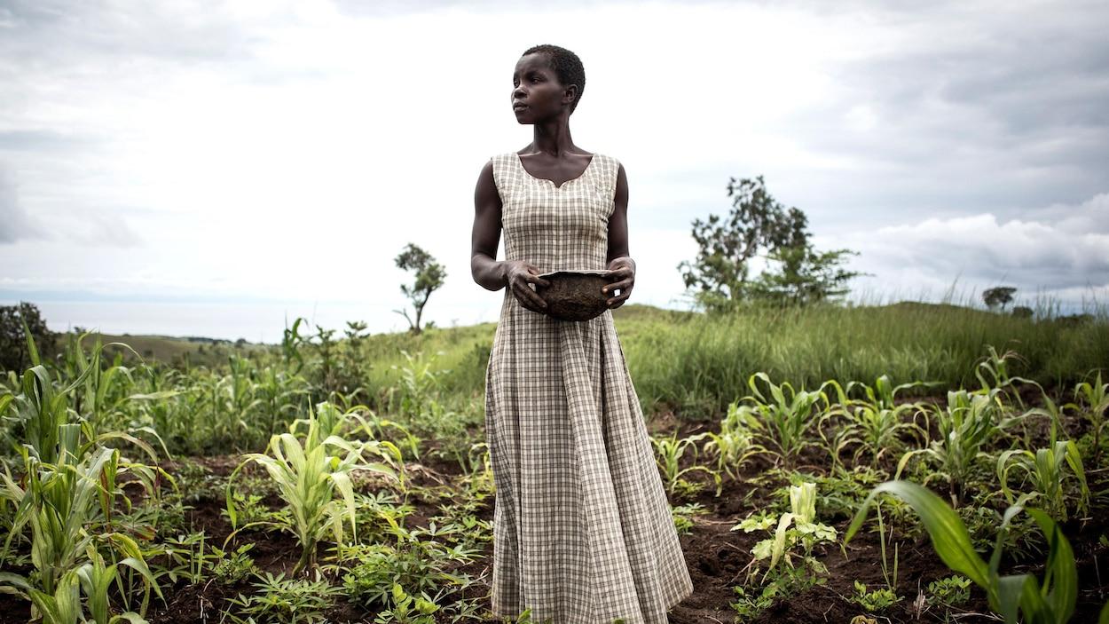 Une femme se tient au milieu de son champs.