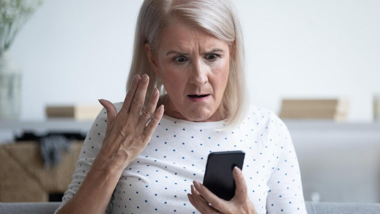 Une femme est exaspérée en regardant son cellulaire.