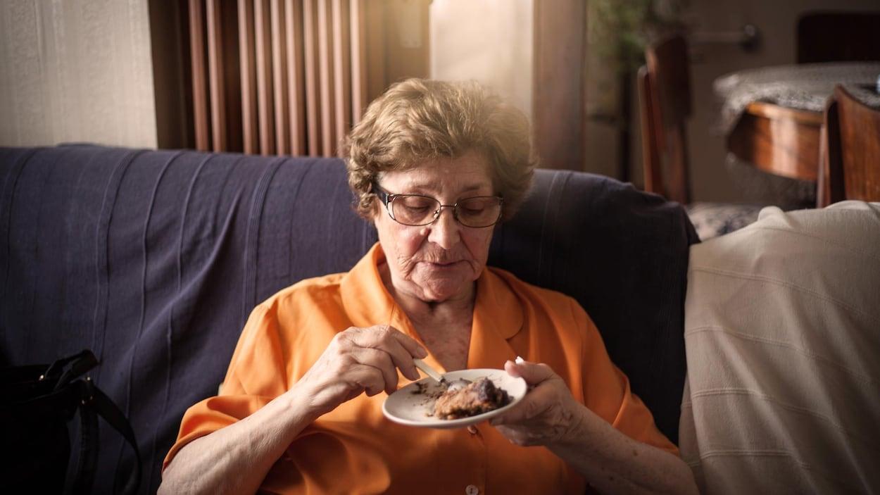 Une dame mange un morceau de tarte au chocolat dans son salon.