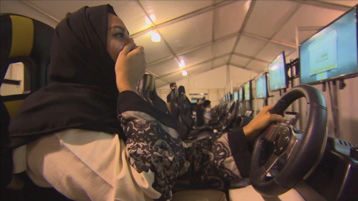 Une femme saoudienne apprend à conduire sur un simulateur.