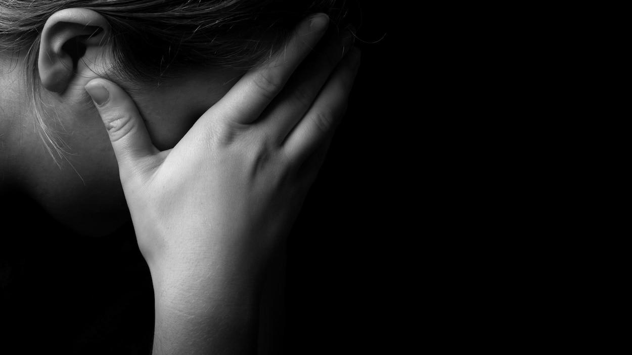 Une femme dans le noir avec sa main sur son oeil.