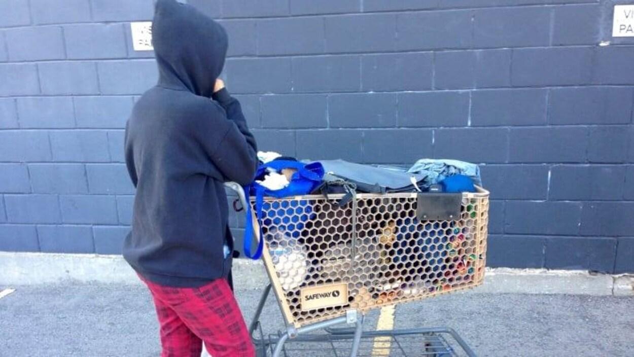 Une femme sans-abris qui pousse un charriot de supermarché.