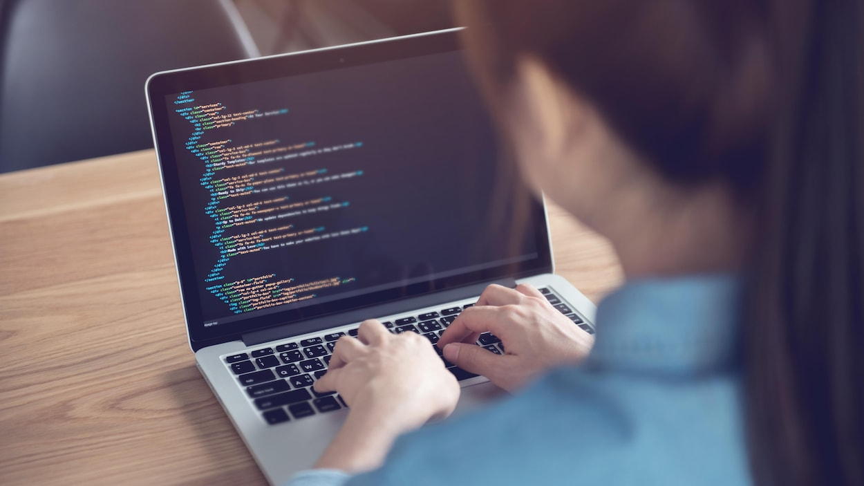 Une femme entrain de coder.