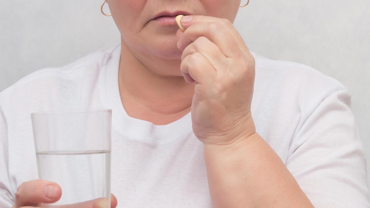 Une femme prend un comprimé avec un verre d'eau.