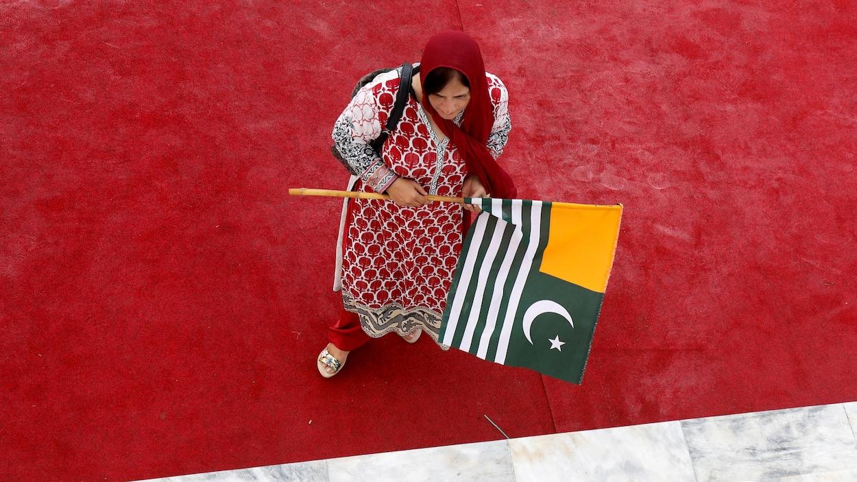Une femme tient le drapeau du Cachemire.