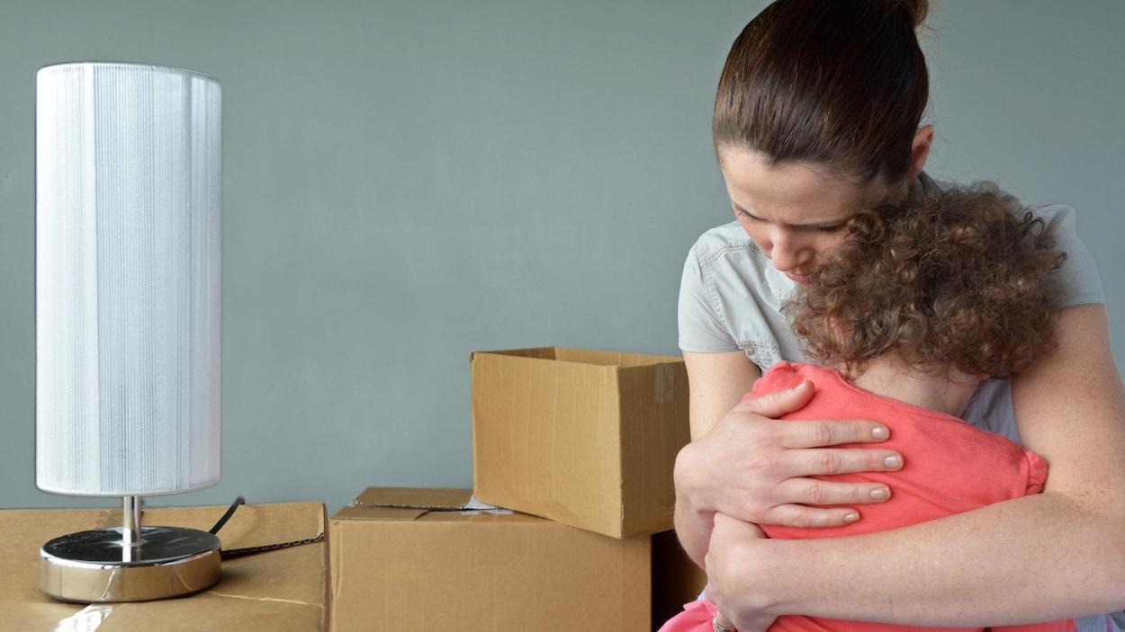 Une femme tient un enfant dans ses bras alors qu'elle a des boîtes de carton autour d'elle