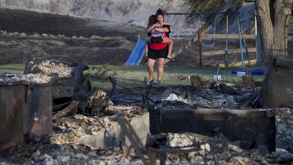 Une mère et sa fille devant les ruines de leur maison de la Première Nation d'Ashcroft, en Colombie-Britannique. Les feux de forêt ont fait rage dans l'intérieur de la province en 2017.