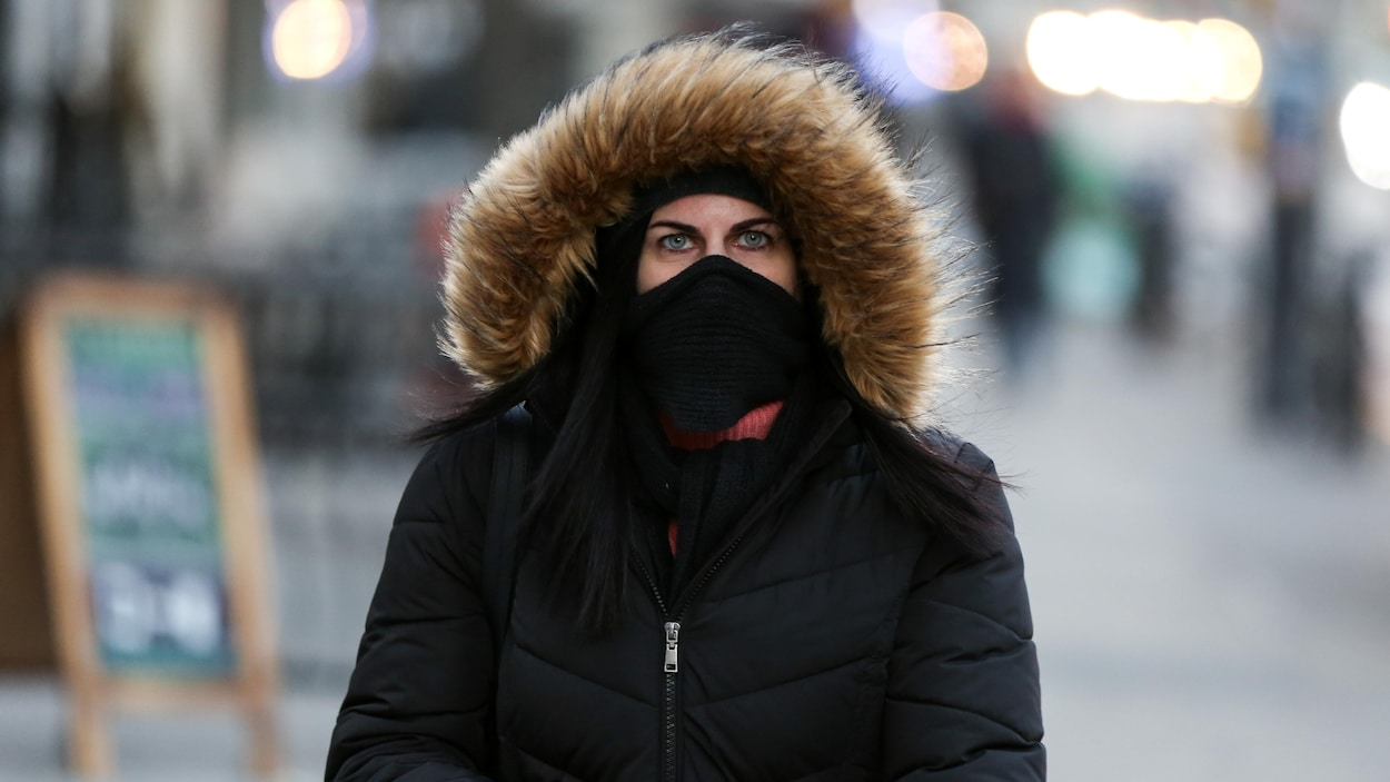 Une femme marche dans le quartier de Manhattan, à New York, qui est balayé par un froid extrême.