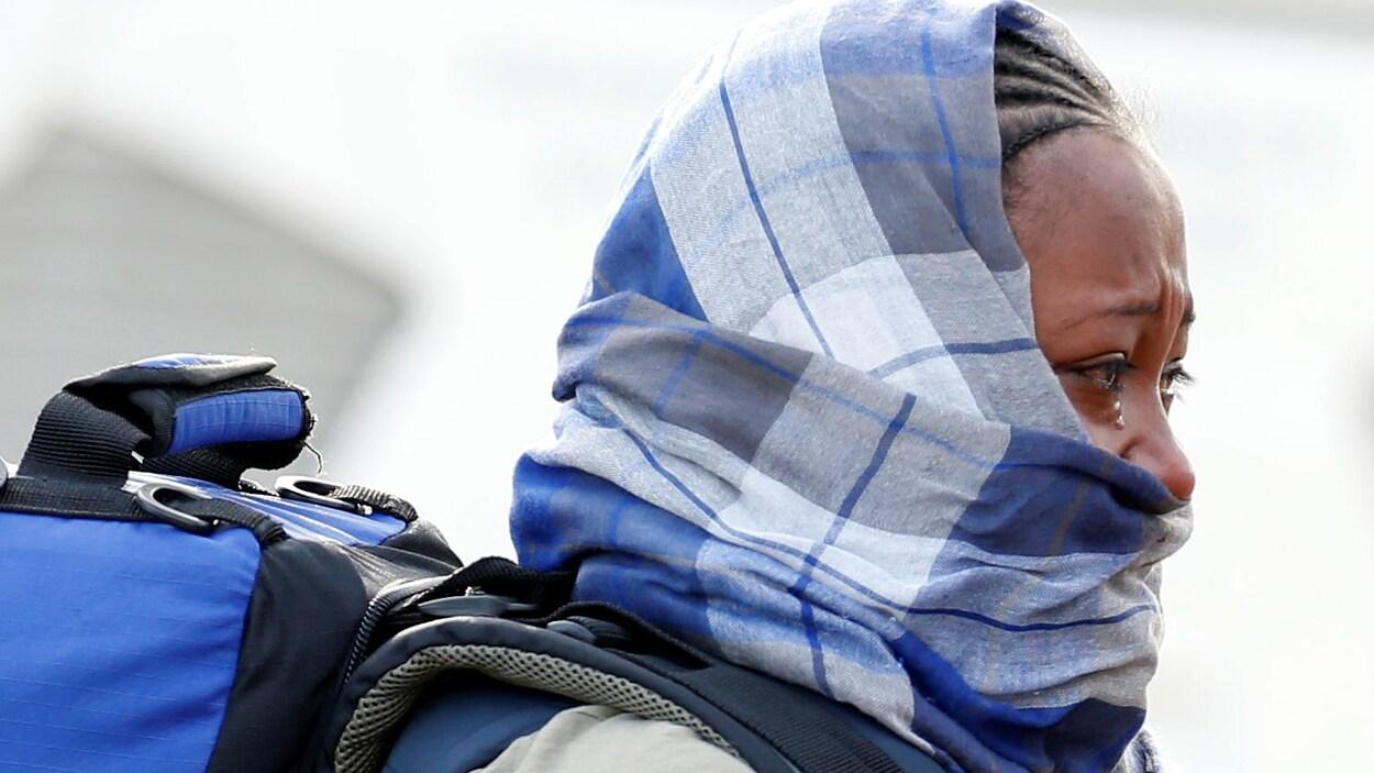 Une femme migrante, la moitié du visage couvert par un foulard, échappe une larme pendant le démantèlement du camp de la « jungle » de Calais.