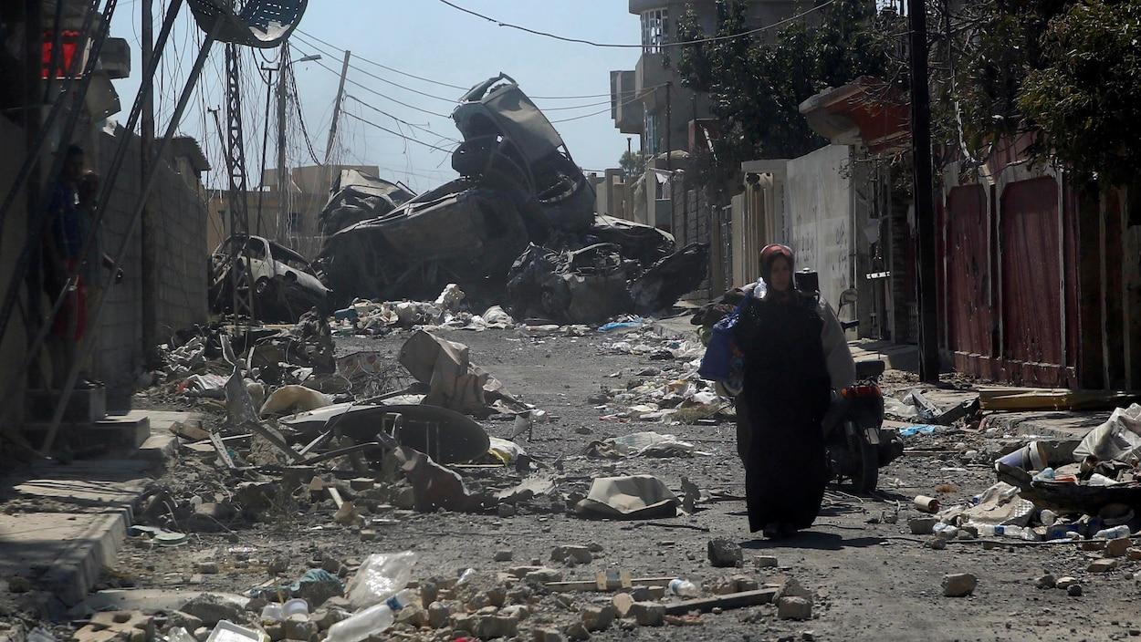 Une femme se promène dans les ruines de la ville de Mossoul, en Irak, où se poursuivent des combats entre les forces armées et les djihadistes du groupe armé État islamique.