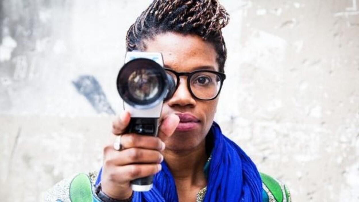 Une femme noire tend devant elle l'objectif d'une caméra.