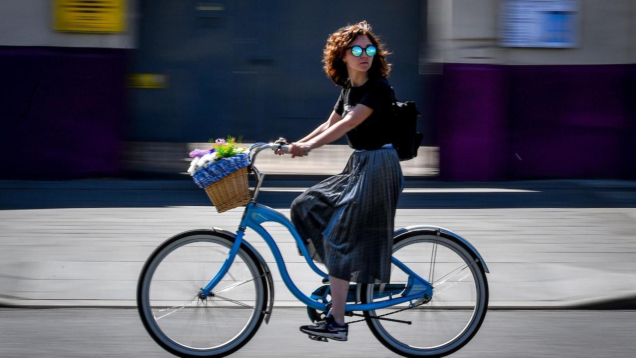 Une femme circule à vélo dans la rue.
