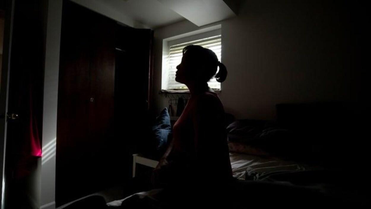 Une femme est assise sur son lit, dans la pénombre du chambre à coucher.