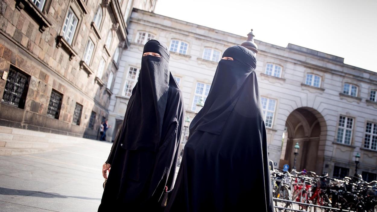Deux femmes voilées marchent dans la rue.