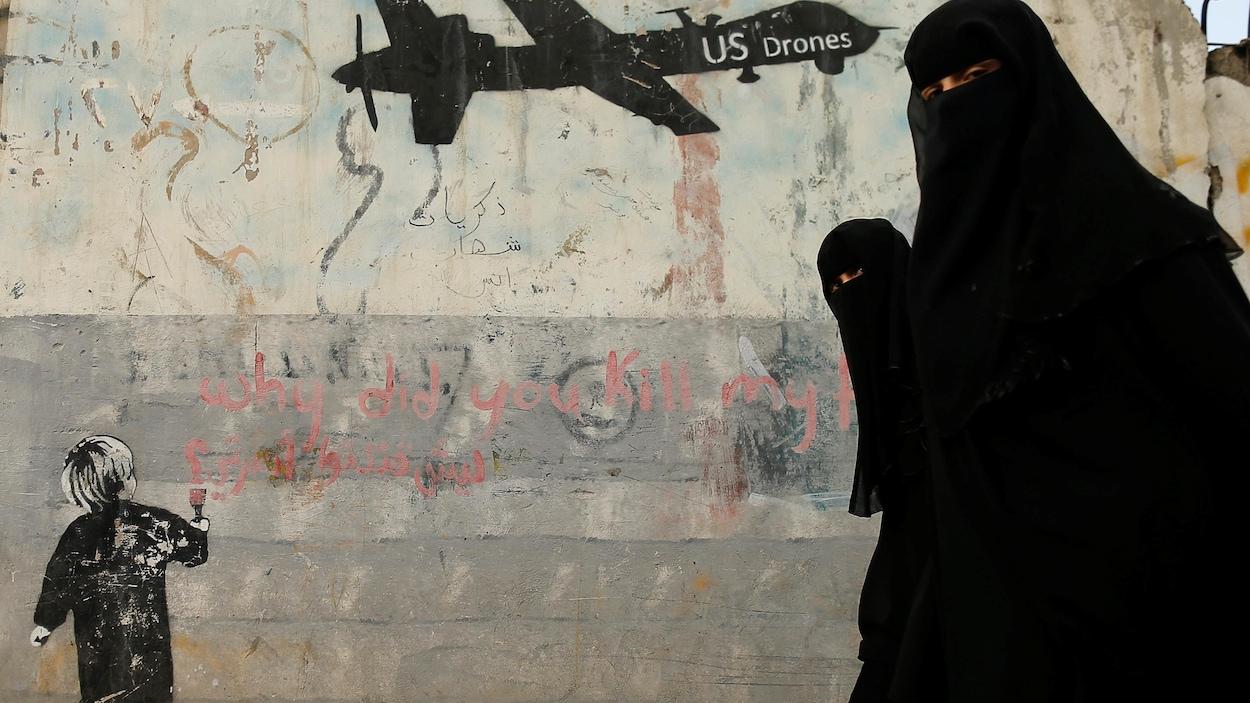 Des femmes passent devant une murale dénonçant les frappes aériennes de la coalition internationale à Sanaa, au Yémen.