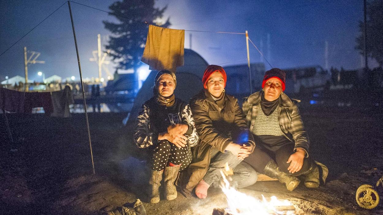 Des migrantes autour d'un feu de camp.