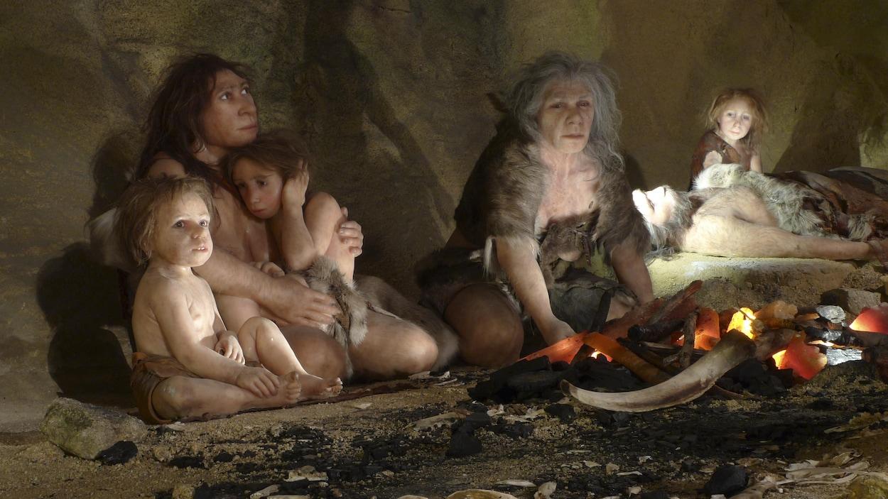 Reconstitution d'une scène de vie de Néandertal dans une caverne. On voit des femmes et des enfants assis autour d'un feu.