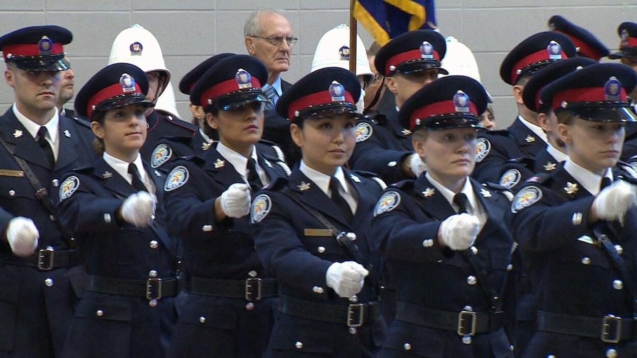Des femmes et des hommes en uniforme de la police de Toronto, en rang, lors d'une cérémonie.
