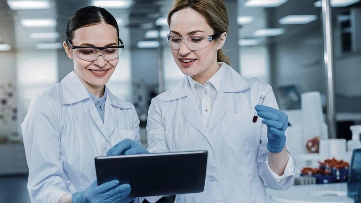 Deux femmes regardent une tablette électronique. Elles portent des gants, des sarraus et des lunettes. Une tient une éprouvette.
