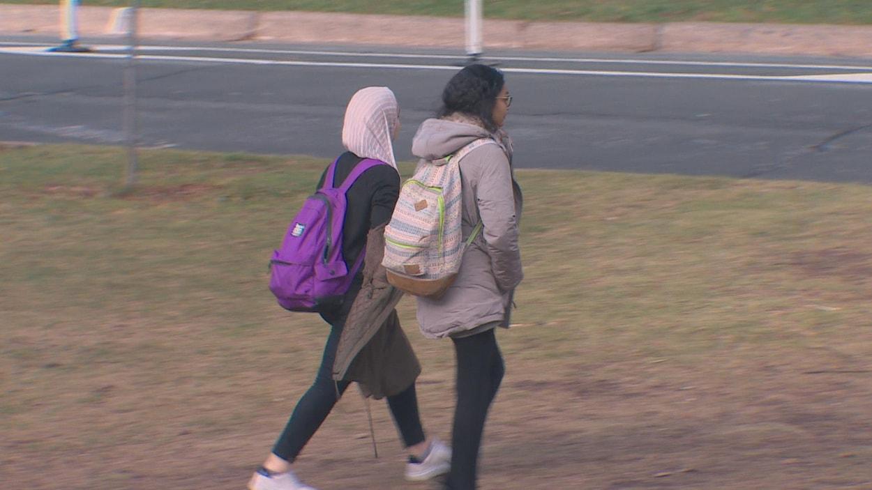 Deux étudiantes, dont une portant un hijab, marchent sur un campus