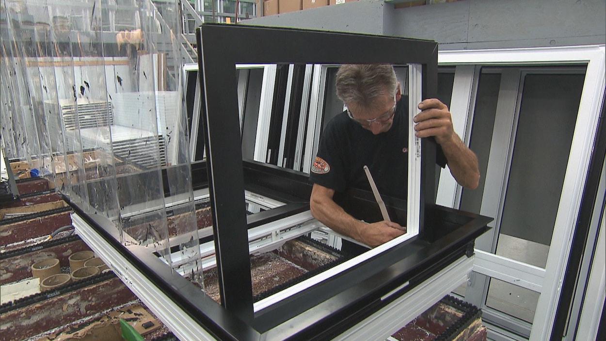 Un homme installe une fenêtre.