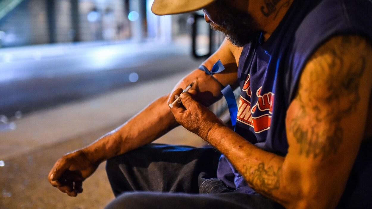 Un homme s'injecte de l'héroïne dans la rue, la nuit.