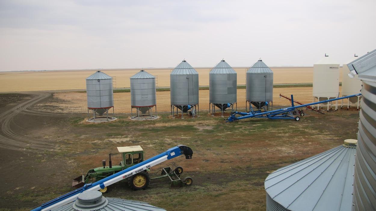 Une ferme avec un tracteur et des compartiments à grain, avec des champs à perte de vue.