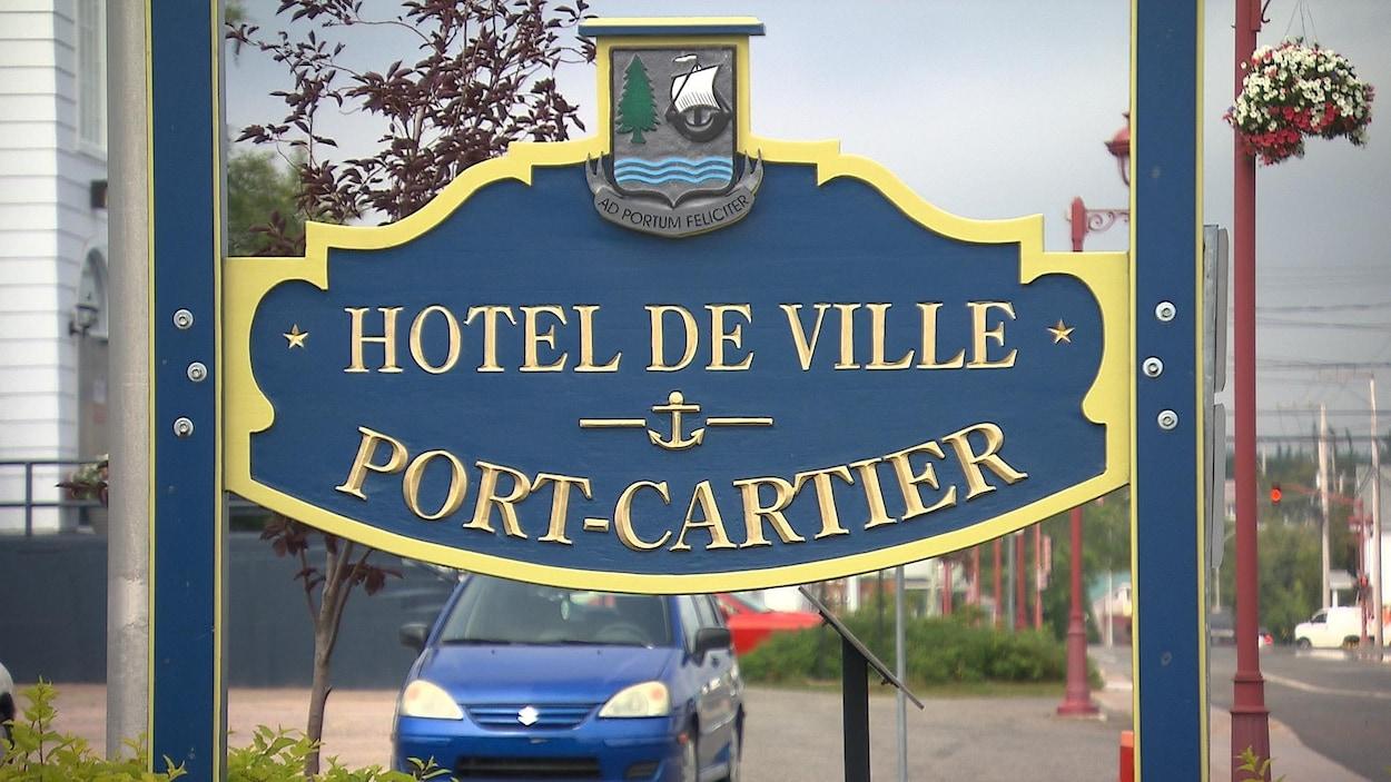 Près de la rue, l'affiche de l'hôtel de ville de Port-Cartier.